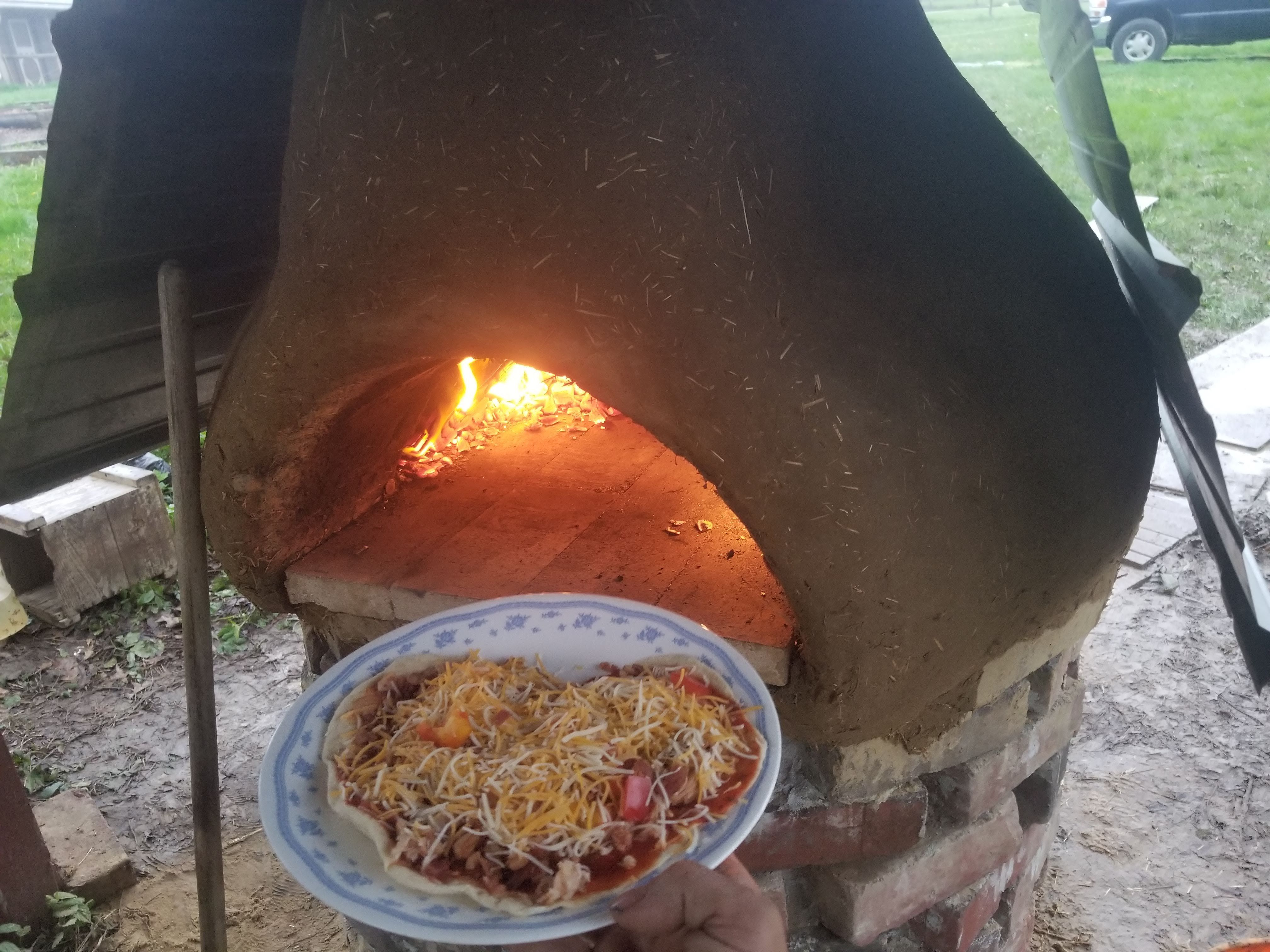Throwing the pizza into the earthen cob oven