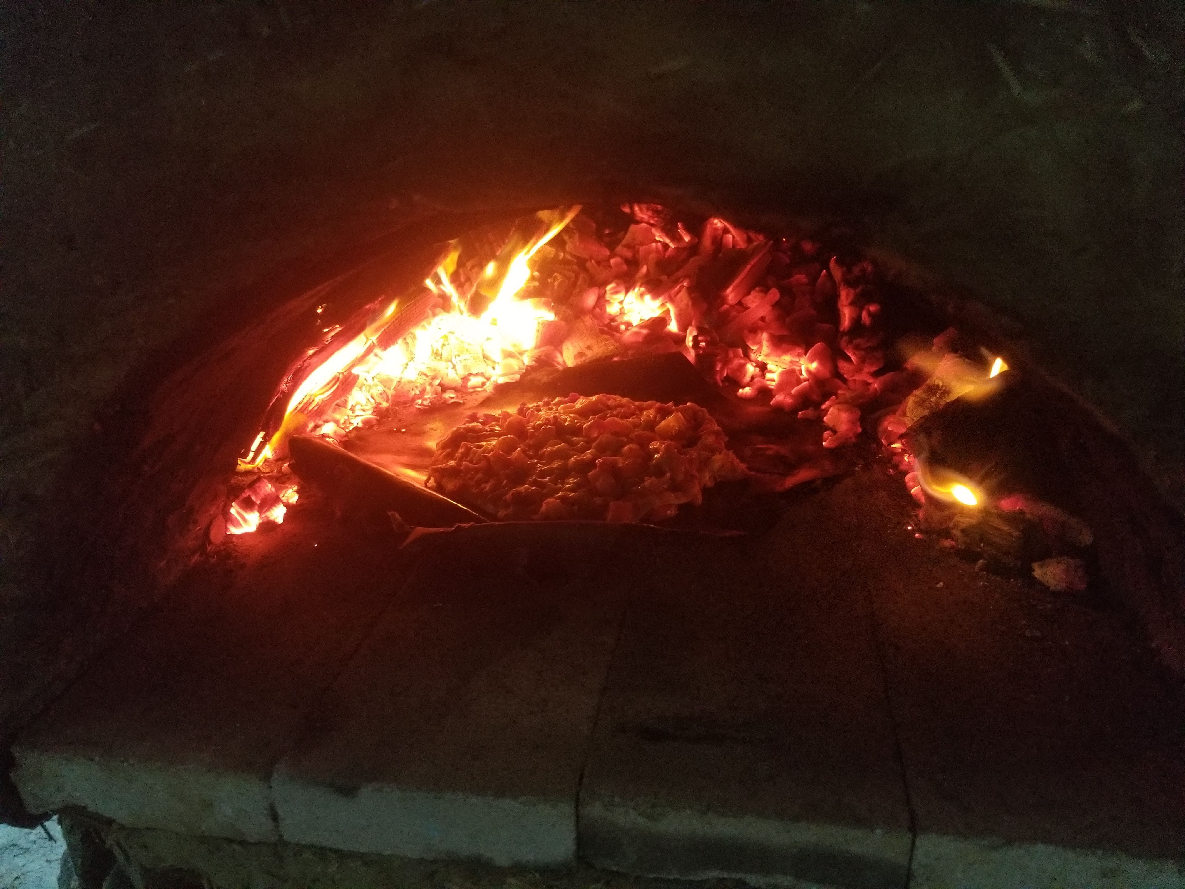 Baking the pizza in the earthen cob oven